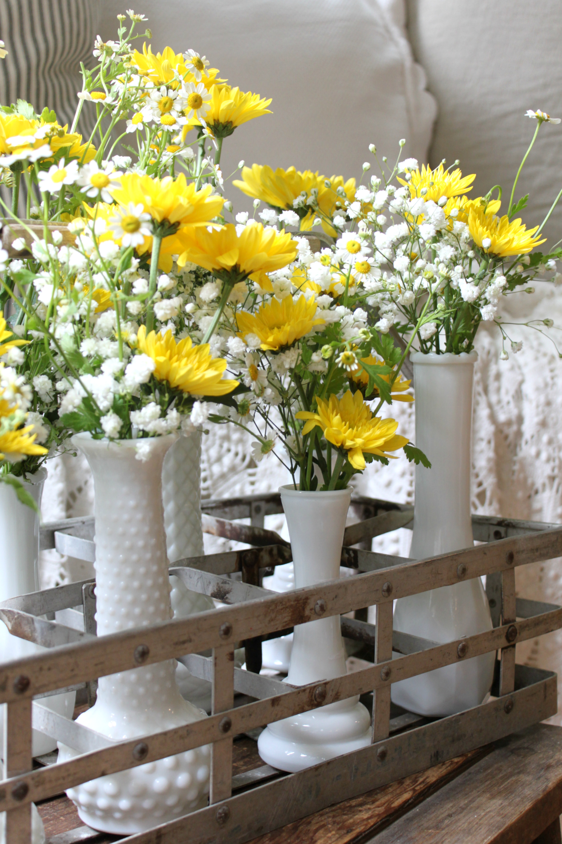 Milk glass vases milk bottle holder floral arrangement an i started by tucking the the babys breath into each vase followed by the yellow daisies at varying heights and then the white daisies to fill in any open mightylinksfo